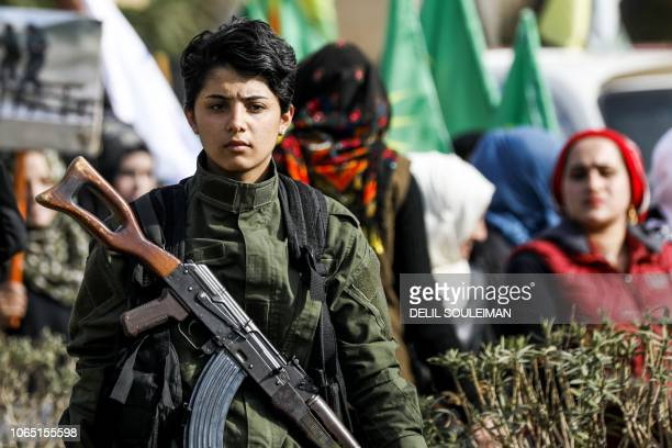 A Syrian Kurdish woman fighter holds a Kalashnikov assault rifle as she stands while others march past during a demonstration in the northeastern...