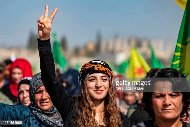 A Syrian Kurdish woman flashes the vsign during a demonstration against Turkish threats in Ras alAin town in Syria's Hasakeh province near the...