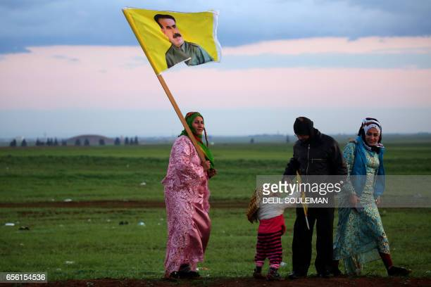 Syrian Kurdish woman holds a portrait of jailed Kurdish rebel chief Abdullah Ocalan during the annual celebrations of Noruz the Persian New Year on...