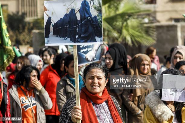 A Syrian Kurdish woman holds up a sign showing a photo depicting fullyveiled women in black garb and walking in chains while marching with others...