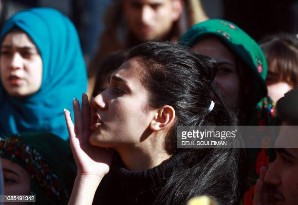 A Syrian Kurdish woman shouts slogans during a demonstration in Qamishli on January 20 marking the first anniversary of the takeover of the northern...