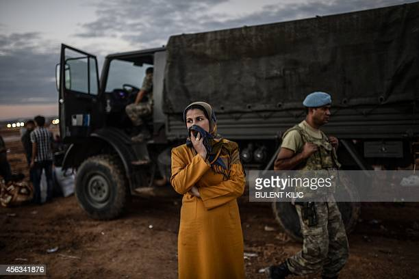 Syrian Kurdish woman stands in front of military truck after crossing the border between Syria and Turkey after several mortars hit both sides near...