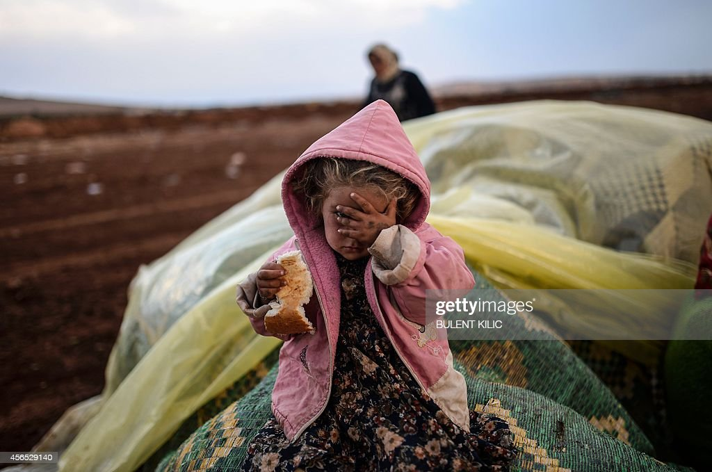 A Syrian Kurdish woman wait with her daughter near the Syria border at the southeastern town of Suruc in the Sanliurfa province after crossing the border between Syria and Turkey after several mortars hit both sides on October 2, 2014. Islamic State fighters are pushing towards a key Kurdish town on Syria's border with Turkey, whose parliament is set on October 2 to consider authorising military intervention against the jihadists on its doorstep. Kurdish fighters backed by US-led air strikes were locked in fierce fighting Wednesday to prevent the besieged border town of Ain al-Arab from falling to the Islamic State group fighters.