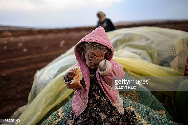 A Syrian Kurdish woman wait with her daughter near the Syria border at the southeastern town of Suruc in the Sanliurfa province after crossing the...