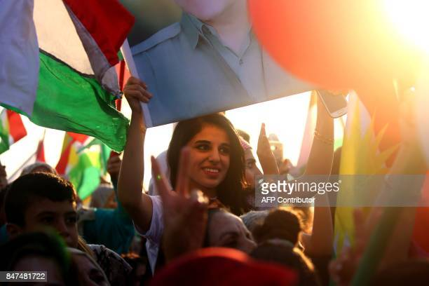 Syrian Kurdish woman waves a flag as she takes part in a rally in the northeastern Syrian city of Qamishli on September 15 in support of an...