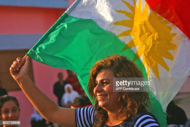 A Syrian Kurdish woman waves a Kurdish flag as she celebrates in the northeastern Syrian city of Qamishli on September 25 in support of the...