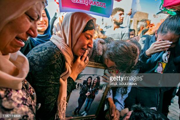 Syrian Kurdish women hold a picture of a relative during the funeral of victims of bombings two days ago in the northeastern city of Qamishli on...