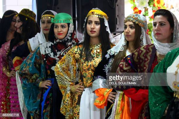 Syrian Kurdish women model traditional Kurdish attire during a fashion show in the northeastern Syrian city of Qamishli on March 10 which coincides...