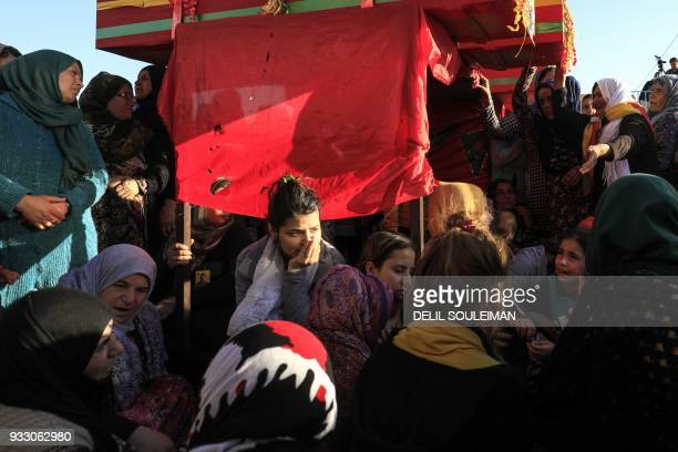 Syrian Kurdish women mourn by the coffins of People's Protection Units fighters during their funeral in the northeastern city of Qamishli on March 17...