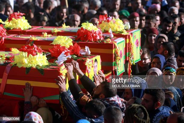 TOPSHOT Syrian Kurds bid their farewell as they mourn by the coffins of People's Protection Units fighters during their funeral in the northeastern...