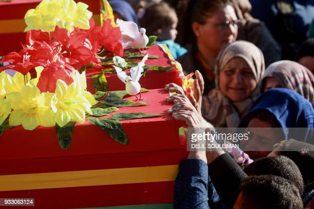 Syrian Kurds bid their farewell as they mourn by the coffins of People's Protection Units fighters during their funeral in the northeastern city of...