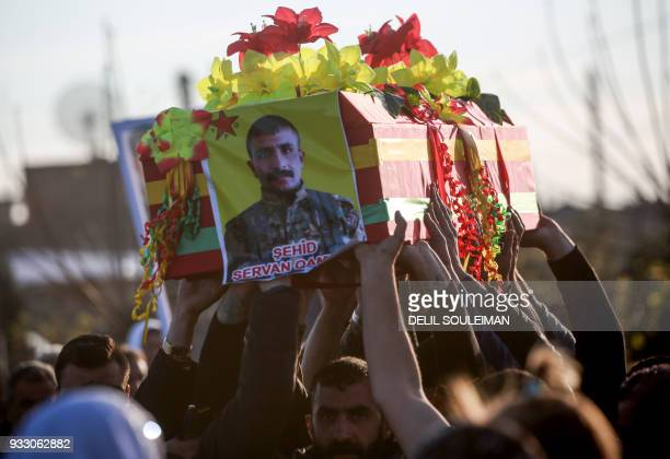 Syrian Kurds carry the coffin of one of the fighters of the People's Protection Units during their funeral in the northeastern city of Qamishli on...