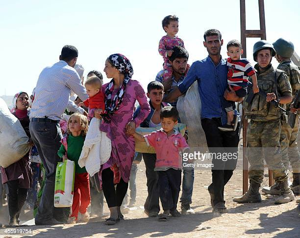 Syrian Kurds carry their belognings after crossing in to Turkey near the Syrian border September 21 2014 near the southeastern town of Suruc in...