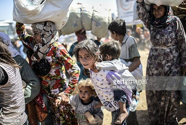 Syrian Kurds carry their belongings after crossing the SyrianTurkish border at the southeastern town of Suruc in Sanliurfa province on September 23...