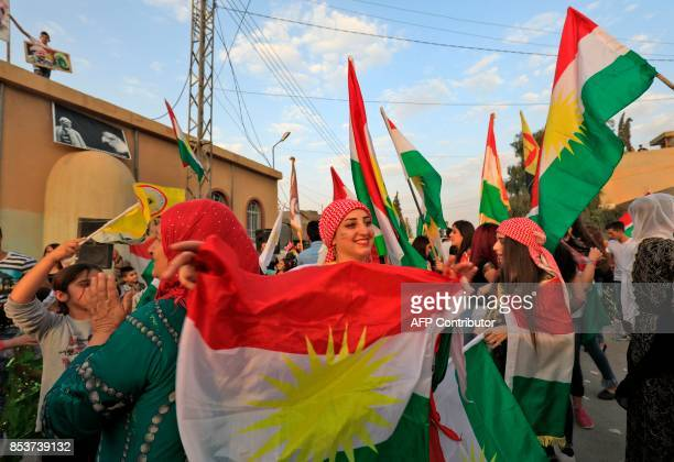 Syrian Kurds dance with the Kurdish flag as they celebrate in the northeastern Syrian city of Qamishli on September 25 in support of the independence...