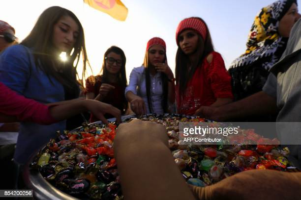 Syrian Kurds distribute sweets in the northeastern Syrian city of Qamishli on September 26 in support of the independence referendum in Iraq's...
