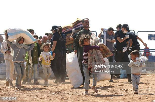 Syrian Kurds fled from clashes between the Islamic State of Iraq and Levant militants and proKurdish Democratic Union Party forces carry their...