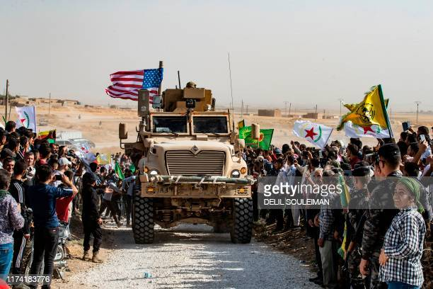 TOPSHOT Syrian Kurds gather around a US armoured vehicle during a demonstration against Turkish threats next to a USled international coalition base...