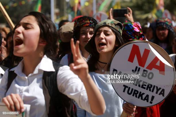 Syrian Kurds hold placards reading 'No to the Turkish occupation' as they take part in a protest in the northeastern city of Amude against the...