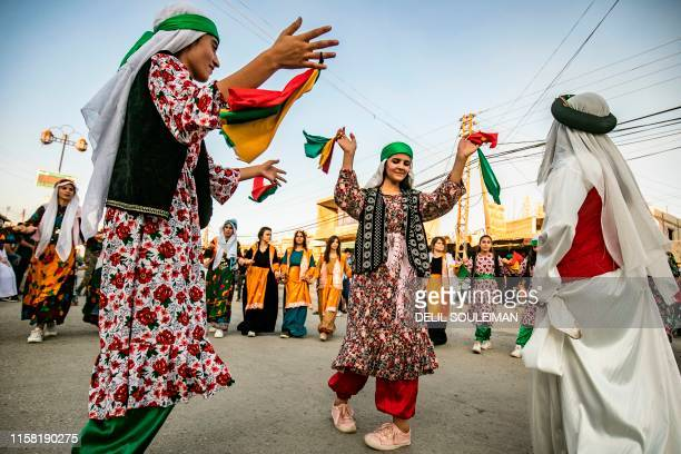 """Syrian Kurds in traditional clothing dance the """"Dabke"""" in a street festival in the city of Rumaylan in Syria's northeastern Hasakeh province on July..."""
