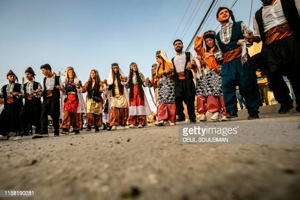 Syrian Kurds in traditional clothing dance the Dabke in a street festival in the city of Rumaylan in Syria's northeastern Hasakeh province on July 27...
