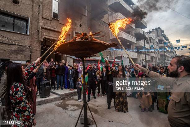 Syrian Kurds light-up a pyre during celebrations of Nowruz, the Persian New Year, in the Kurdish-majority city of Qamishli in Syria's northeastern...