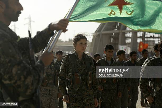 TOPSHOT Syrian Kurds march during the funeral of fighters who died during an assault launched by Arab and Kurdish forces against Islamic State group...