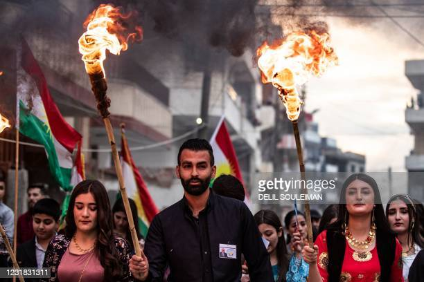 Syrian Kurds march with torches during celebrations of Nowruz, the Persian New Year, in the Kurdish-majority city of Qamishli in Syria's northeastern...