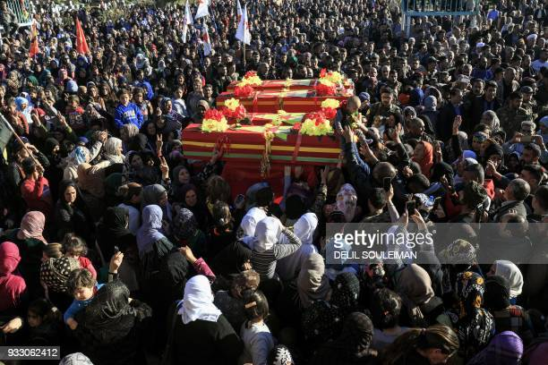 Syrian Kurds mourn by the coffins of People's Protection Units fighters during their funeral in the northeastern city of Qamishli on March 17 after...