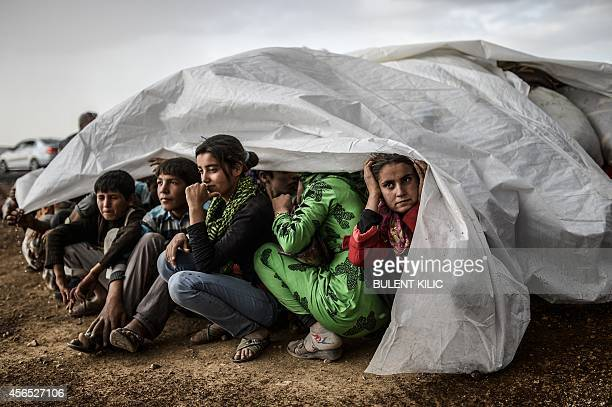 Syrian Kurds take cover from the rain in the southeastern town of Suruc in the Sanliurfa province after crossing the border between Syria and Turkey...