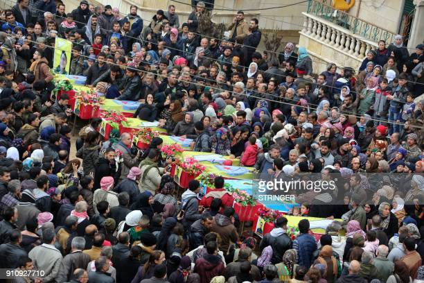 TOPSHOT Syrian Kurds take part in a funeral for Kurdish People's Protection Units militia fighters and civilians who died in clashes with Turkish...