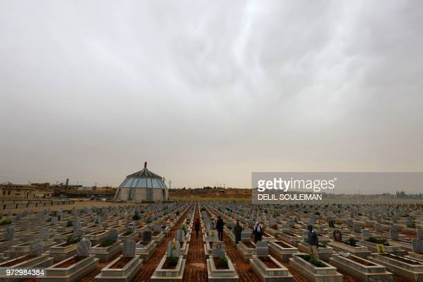 Syrian Kurds visit on May 28, 2018 the tombs of loved ones at a cemetery set up in 2012 which houses the remains of civilians and fighters who lost...