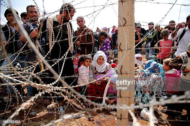 Syrian Kurds wait behind the border fences to cross into Turkey near the southeastern town of Suruc in Sanliurfa province on September 28, 2014 in...