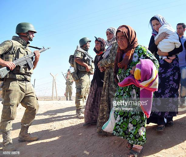 Syrian Kurds walk after crossing into Turkey at the Turkish-Syrian border, September 20, 2014 near the southeastern town of Suruc in Sanliurfa...