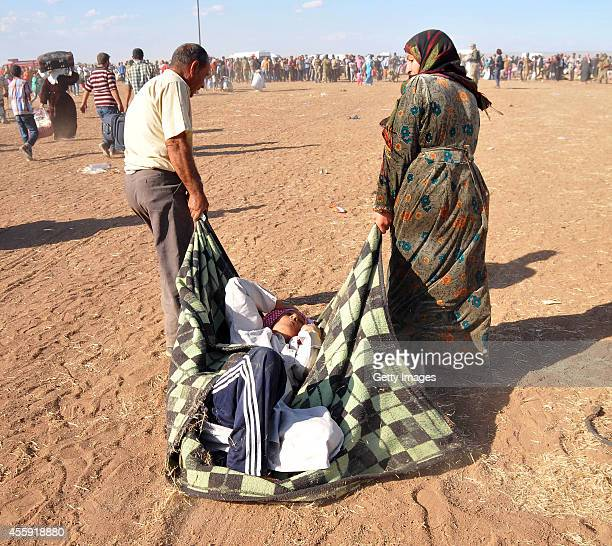 Syrian Kurds walk after crossing into Turkey at the TurkishSyrian border September 20 2014 near the southeastern town of Suruc in Sanliurfa province...