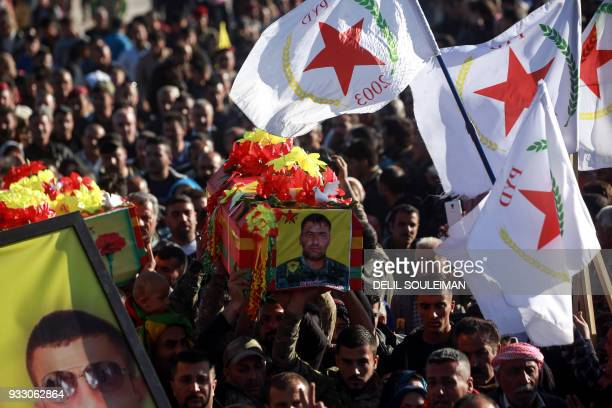 Syrian Kurds wave flags of the Kurdish Democratic Union Party as they carry the coffin of one of the fighters of the People's Protection Units during...