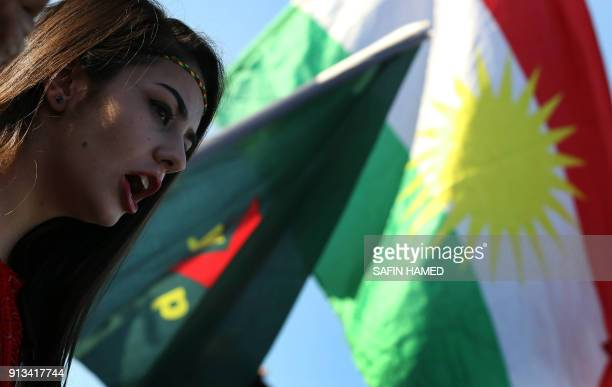 Syrian Kurds wave the Kurdish flag and flags bearing the logos of the People's Protection Units Women's Protection Units as they chant slogans in the...