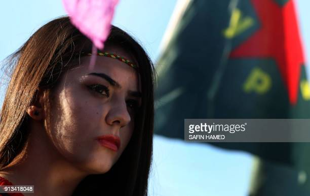 TOPSHOT Syrian Kurds wave the Kurdish flag and flags bearing the logos of the People's Protection Units Women's Protection Units as they chant...