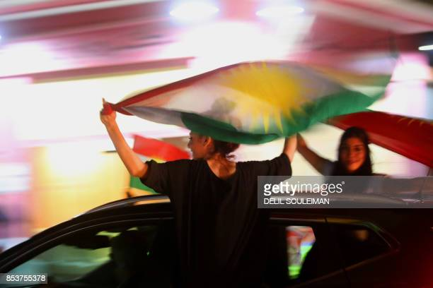 Syrian Kurds wave the Kurdish flag as they celebrate in the northeastern Syrian city of Qamishli on September 25 in support of the independence...