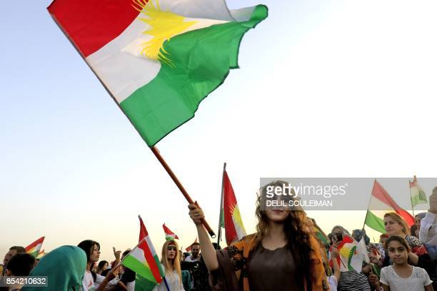 Syrian Kurds wave the Kurdish flag in celebration in the northeastern Syrian city of Qamishli on September 26 in support of the independence...