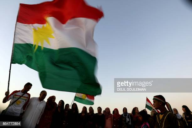 Syrian Kurds wave the Kurdish flag, in the northeastern Syrian city of Qamishli on September 27 during a gathering in support of the independence...