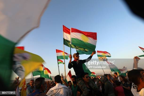 Syrian Kurds wave the Kurdish flag in the northeastern Syrian city of Qamishli on September 27 during a gathering in support of the independence...
