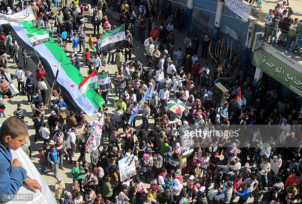 Syrian Kurds waving the Kurdish and Syrian flags march during an antiregime protest in the city of Qamishli on the border with Turkey on March 23...