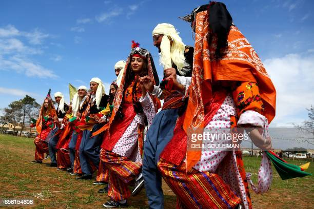 Syrian Kurds wearing traditional outfits take part in the annual celebrations of Noruz the Persian New Year on March 21 in the northeastern Syrian...