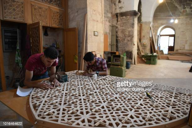 Syrian labourers take part in renovation work at the historic Grand Umayyad mosque in the northern Syrian city of Aleppo on August 14 almost two...