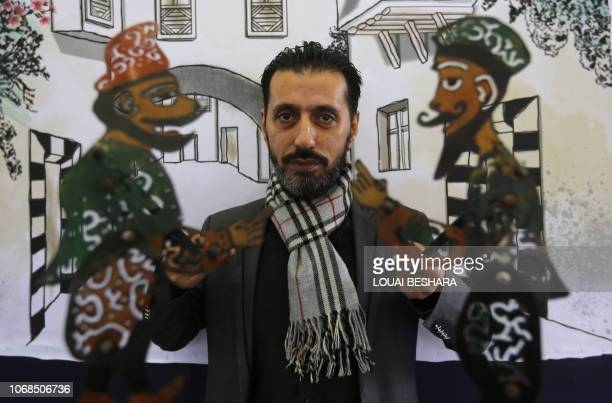 Syrian last shadow puppeteer Shadi alHallaq holds his puppets Karakoz and Eiwaz before a presentation in Damascus on December 3 2018 Syrians last...