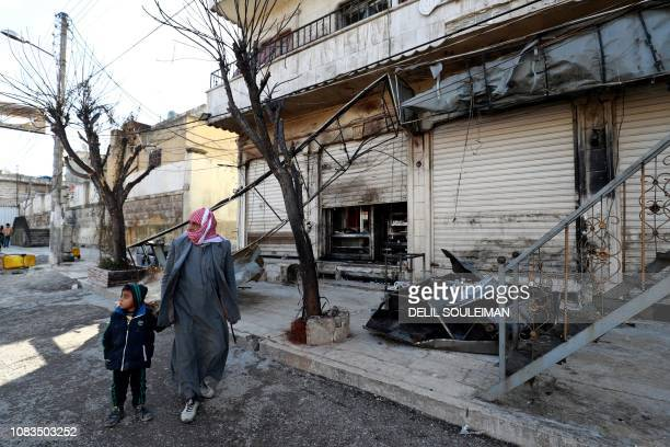 A Syrian man and child walk past the shuttered doors of a restaurant which was the site of a suicide attack targeting USled coalition forces in the...