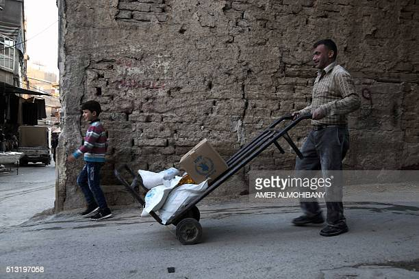 A Syrian man and his child carry sacks of wheat and aid provided by the World Food Programme in Kafr Batna in the rebelheld Eastern Ghouta area on...