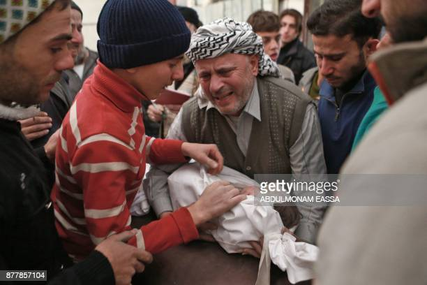 A Syrian man and his son mourn over the body of a young girl who died during a reported air strike in the rebelheld besieged town of Arbin in the...