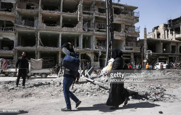 A Syrian man and woman carrying children walk during the evacuation from the town of Arbin in the Eastern Ghouta region on the outskirts of the...